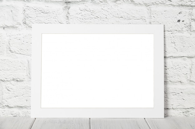 White empty photo frame against brick wall. mockup with copy space