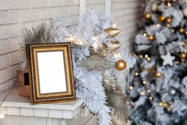 White empty photo frame on the fireplace. christmas white interior with bokeh defocused effect