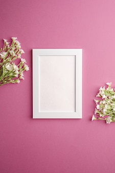 White empty photo frame mockup with mouse-ear chickweed flowers on pink purple background, top view copy space