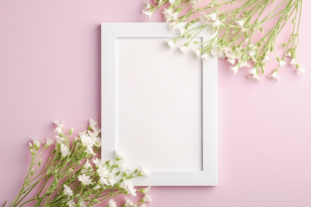 White empty photo frame mockup with mouse-ear chickweed flowers