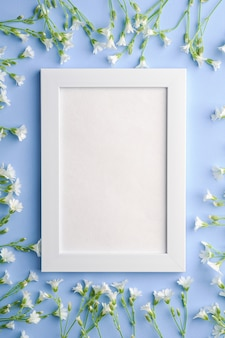 White empty photo frame with mouse-ear chickweed flowers on blue background, top view copy space