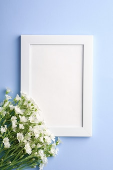 White empty photo frame with mouse-ear chickweed flowers on blue table, top view copy space