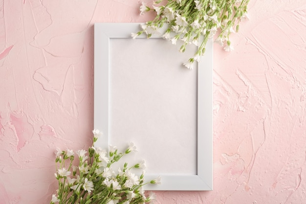 White empty photo frame with mouse-ear chickweed flowers on pink background, top view copy space