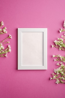 White empty photo frame with mouse-ear chickweed flowers on pink purple background, top view copy space