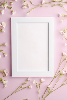 White empty photo frame with mouse-ear chickweed flowers on pink table, top view copy space