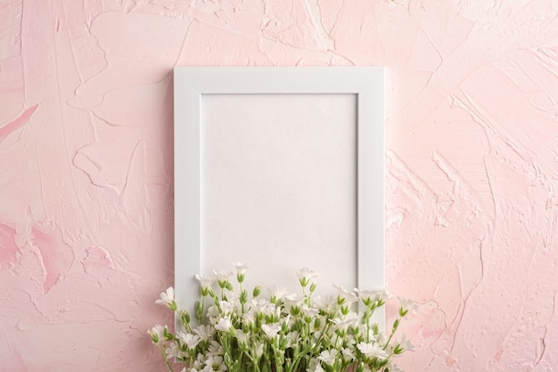 White empty photo frame with mouse-ear chickweed flowers on pink textured table, top view copy space