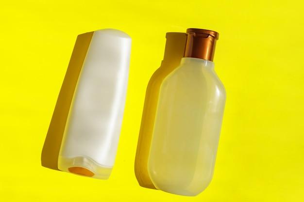 黄色の背景に白い空のプラスチック製の化粧品ボトル。プラスチック廃棄物。プラスチックとエコロジーのリサイクルの概念。