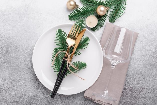 Белая пустая тарелка, стекло, подарки и еловая ветка на каменном фоне. сервировка новогоднего стола. вид сверху - изображение