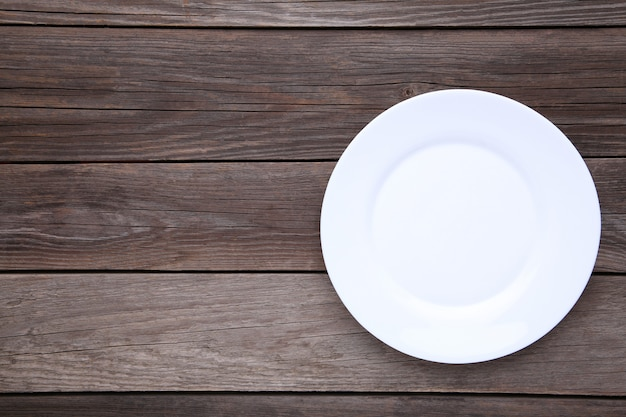 White empty plate on a grey wooden background