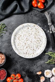 新鮮な生野菜、野菜の中心にある白い空の皿。健康的でクリーンな食事、ビーガン、ダイエット食品のコンセプト。黒の背景