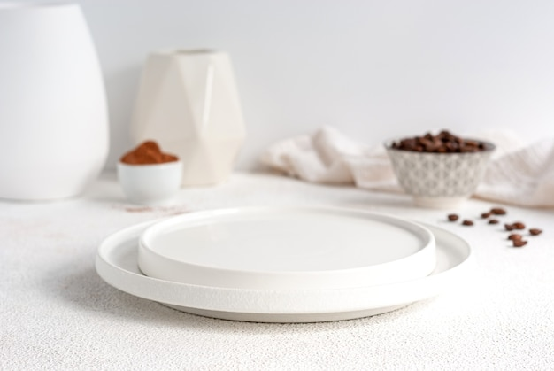 Белая пустая тарелка на столе с кофе и кокаином на фоне - десерт или макет торта