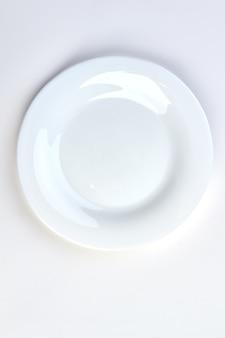 白い背景の上の白い空のプレート。白、上面図に分離された白いセラミックプレート。