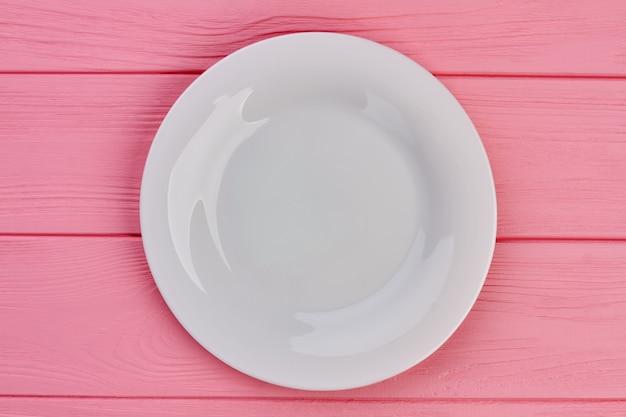 木製の背景に白い空のプレート。ピンクの木製テーブル、上面図のセラミックプレート。