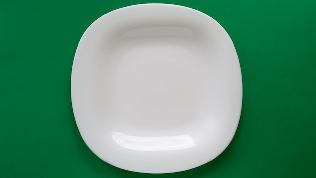 White empty plate on a wide dark green background with a place for food in vintage minimal style close-up