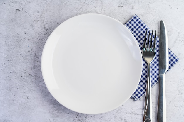 White empty plate with fork and a knife on a blue-white tablecloth.