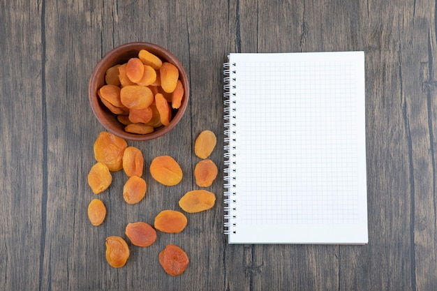 White empty sheet of paper with dried apricots placed on wooden table .