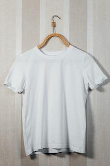 Белые пустые футболки с деревянной вешалкой на сером пространстве