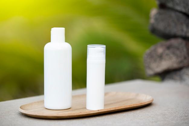 竹皿にスキンケアボトルの白い空のチューブ