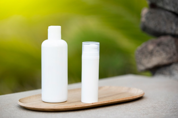 White empty tube of skincare bottle on bamboo plate