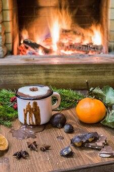 Белая эмалированная кружка с горячим шоколадом перед уютным камином.