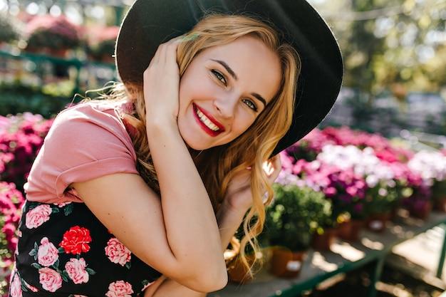 꽃으로 인물 촬영하는 동안 행복을 표현하는 흰색 매혹적인 여자. 자연에 앉아 모자에 매력적인 백인 모델의 초상화