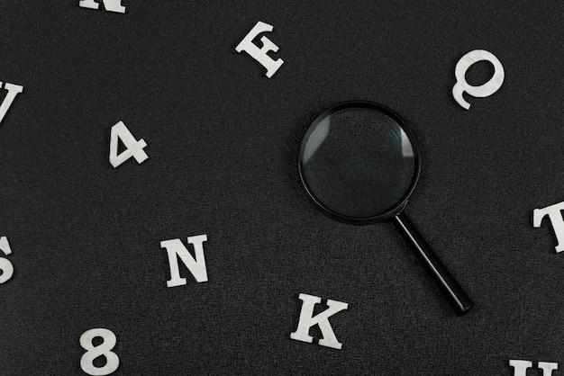 검은 공간에 흰색 영어 문자와 숫자 및 돋보기. 검색 개념