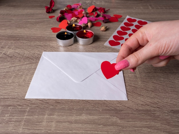 White envelope next to candles with red rose petals on the table and a woman's hand holding a heart