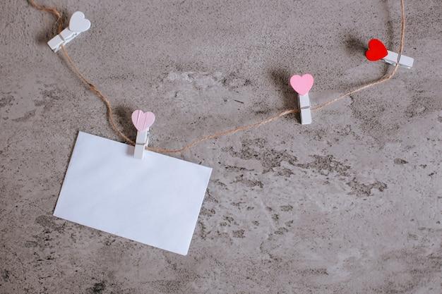 미니 하트 모양의 옷 라인 로프에 꼬인 흰 봉투