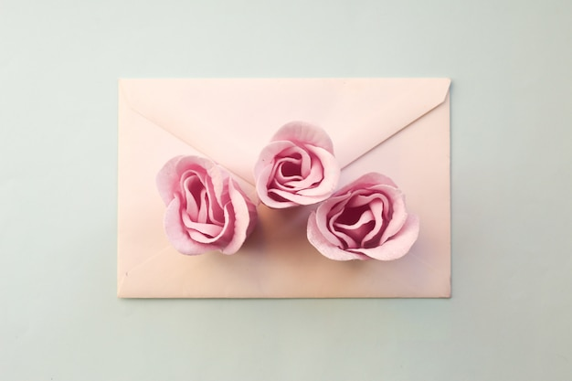 White envelope, three pink rose flowers on a blue background. minimal flat lay