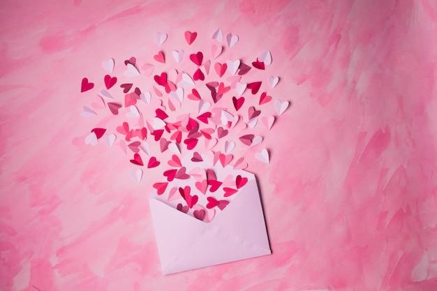 Белый конверт с бумажными сердечками на розовом