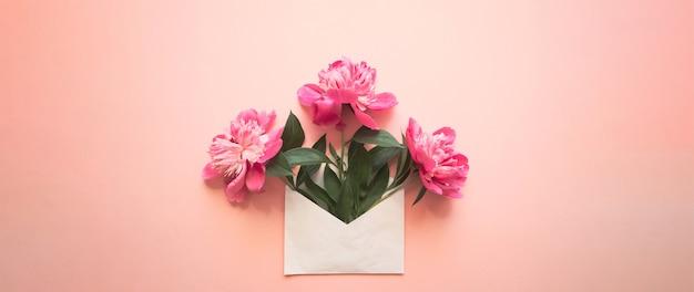 Белый конверт с розовыми пионами внутри на розовом фоне шаблон для информационных бюллетеней и другой почты