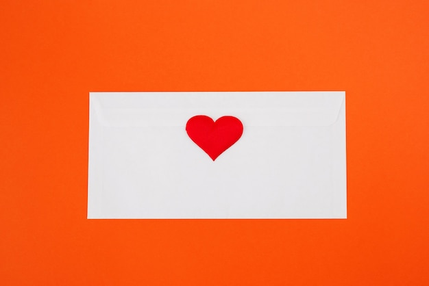White envelope with a red heart on an orange background. view from above. flat lay.