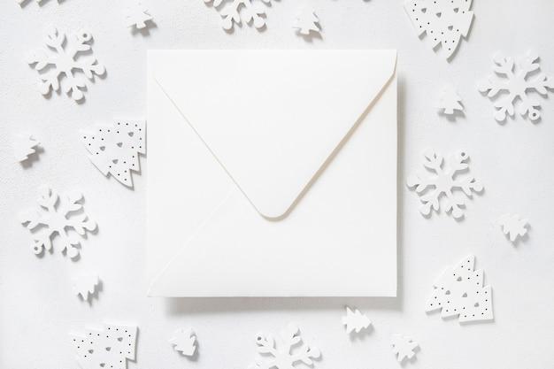 白い背景の上の白いクリスマスの装飾と白い封筒。雪片の上面図とクリスマスと新年の挨拶テンプレート。休日のモックアップ。