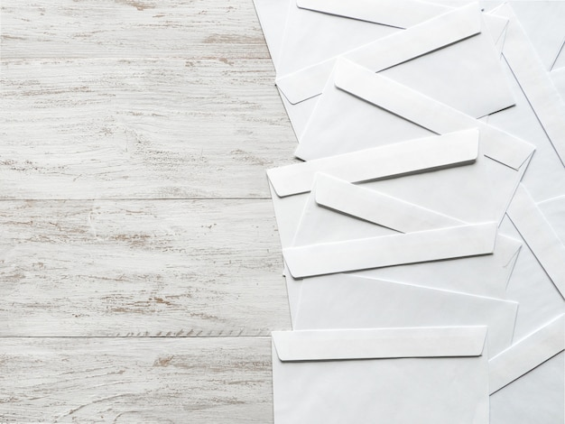 White envelopes are laid out on a wooden table
