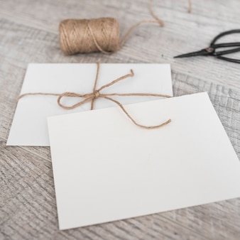 White envelopes with strings and scissor on wooden background