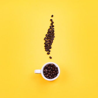 White espresso cup with beans in shape of coffee steam, yellow background. flat lay