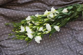 White eustoma bouquet on gray design textile