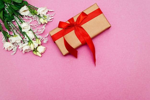 白いトルコギキョウの花とギフトボックスピンクの背景。母の日、誕生日、バレンタインデー、女性の日、お祝いのコンセプト。ソフトセレクティブフォーカス。スペースをコピーします。