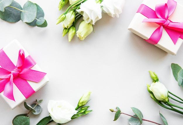 White eustoma flowers and gift box on white background