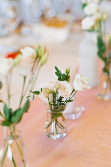 ガラスの花瓶に白いトルコギキョウの花がテーブルの上に立っています。結婚式の宴会テーブル
