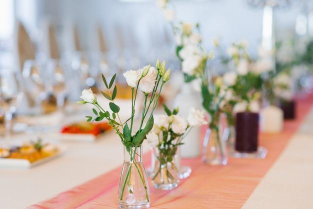 白いトルコギキョウの花は結婚式でお祝いテーブルにガラスの花瓶に立つ
