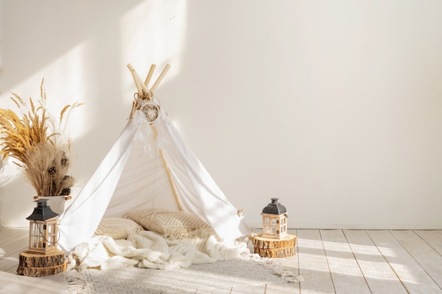 Белый тканевый вигвам и индейский декор в интерьере детской комнаты с копией пространства.