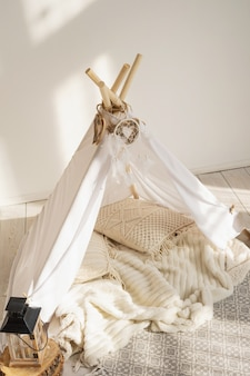 White fabric wigwam and native american decor in a children's room on a sunny day.