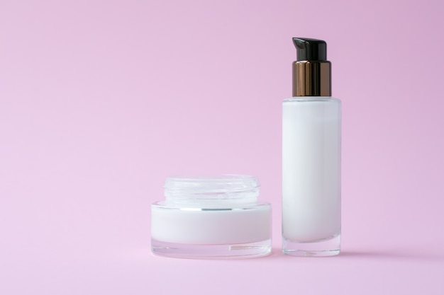 White face cream in a jar and moisturizing lotion in a glass bottle on pink paper background.