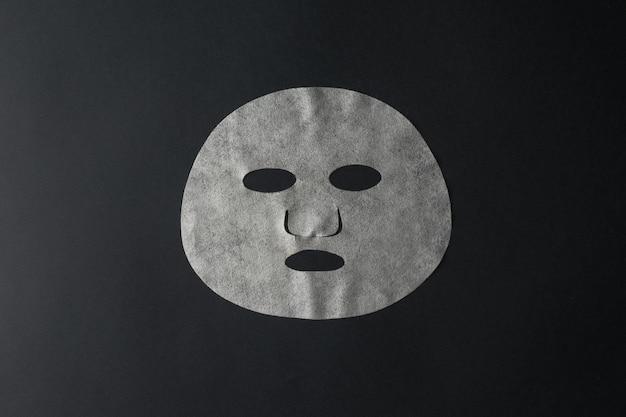 Белая маска для лица на черном фоне. маска для ухода за лицом и изменения внешности.