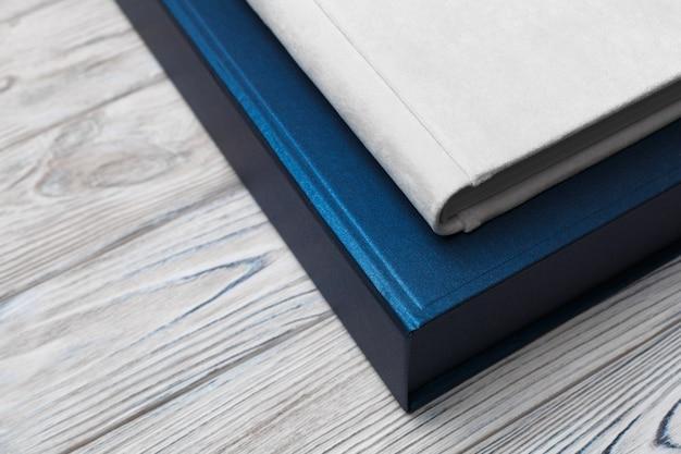 Белая книга семейного фото с тканевым переплетом на конце картонной коробки вверх. свадебный фотоальбом с коробкой на деревянной стене с пространством для текста. фотоальбом с красивой стильной обложкой