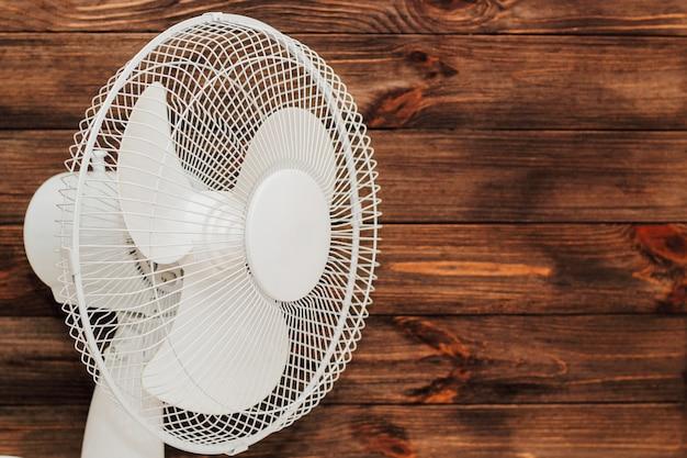 Белый вентилятор с лопастями для охлаждения помещения в жару на деревянном фоне.