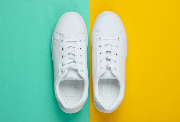 White fashion sneakers on two colored paper