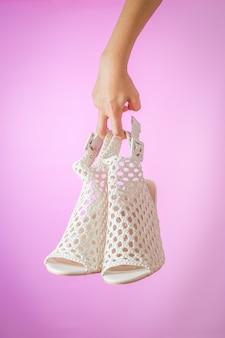 Белые модные женские летние туфли в руке на фиолетовой поверхности