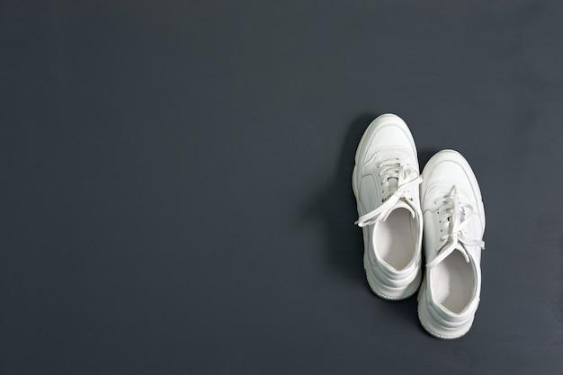 コピースペースを持つ灰色のテーブルの女性のための白いおしゃれな革スニーカー。厚底のスニーカー。